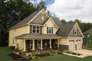 Large house wrapped in yellow vinyl siding