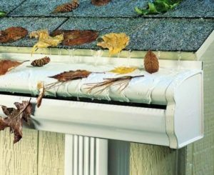 A gutter system with a curved hood keeping leaves and debris out of the trough